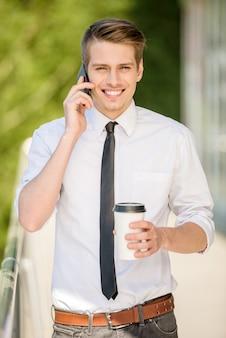 O homem vestiu a fala formal no telefone durante o coffeebreak.