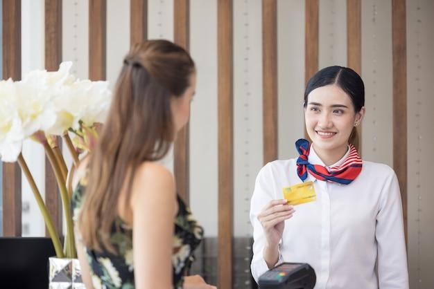 O hóspede faz o pagamento com cartão para serviços no balcão de check-in do hotel, os clientes fazem o check-in em um resort