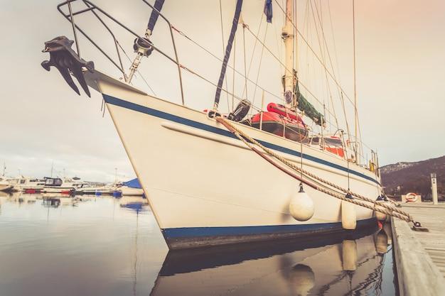 O iate grande da navigação amarrou ao pontão no porto.