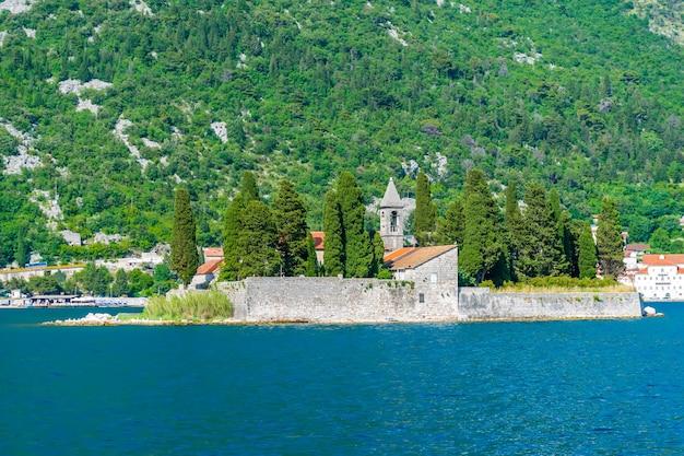 O iate navega perto da pitoresca ilha de st george, na baía de kotor.