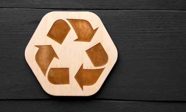 O ícone de reciclagem de madeira em cima da mesa