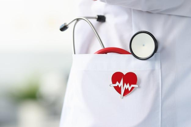 O ícone do estetoscópio e do coração mentem no jaleco branco do médico. conceito de consulta de cardiologista