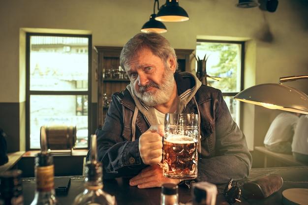 O idoso barbudo bebendo cerveja em um bar