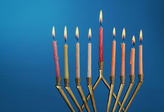 O iluminado de velas de hanukkah em menorah em fundo azul