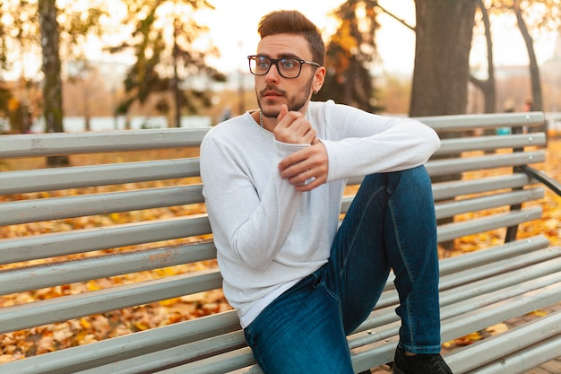 O indivíduo considerável novo do moderno está sentando-se no parque do outono em um banco.