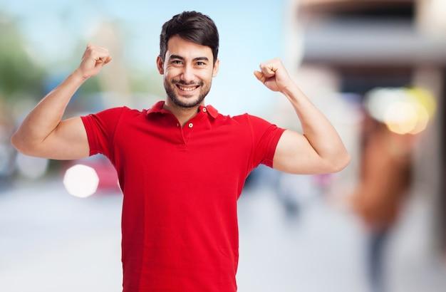 O indivíduo de sorriso que mostra seus músculos