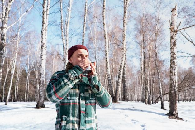 O indivíduo do sexo masculino bebe de um copo em uma floresta de inverno nevado. homem de camisa quadriculada mantém a xícara de café ao ar livre e goza de bom tempo
