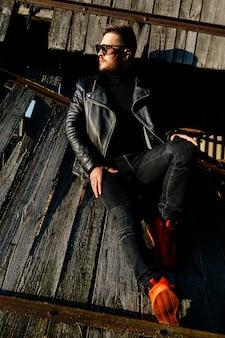 O indivíduo farpado nos óculos de sol em uma jaqueta de couro senta-se