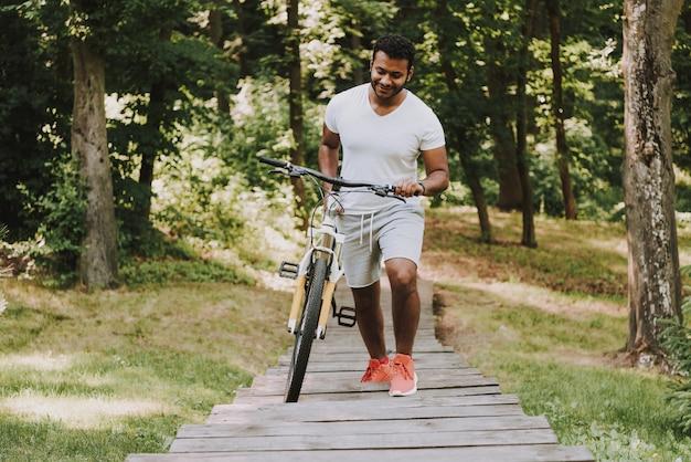 O indivíduo latin está rolando a bicicleta na passagem de madeira.