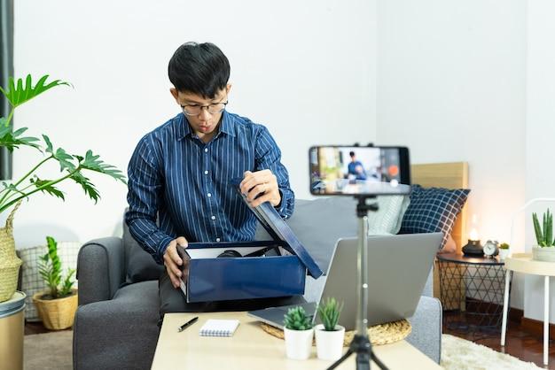 O influenciador de mídia social apresenta e analisa a gravação ou streaming de vlog sobre o produto usando smartphone no tripé