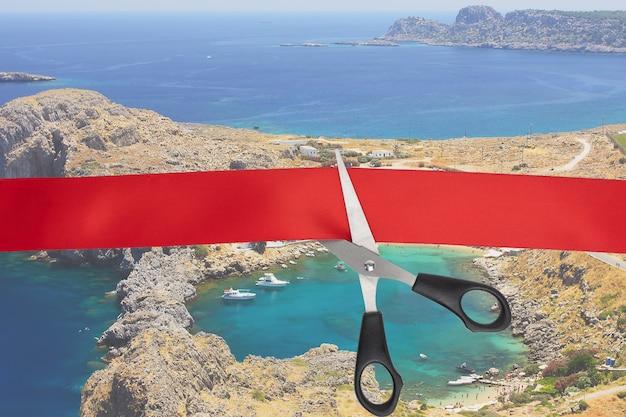 O início da temporada turística, o fim da quarentena, a abertura das fronteiras dos países. uma tesoura corta uma fita vermelha com vista para a baía em forma de coração na ilha de rodes, grécia