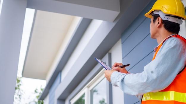 O inspetor ou engenheiro está verificando a estrutura do edifício e as especificações do telhado da casa