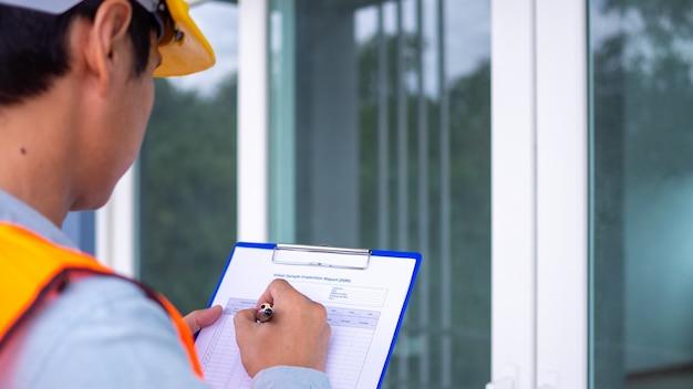 O inspetor ou engenheiro está verificando a estrutura do edifício e os requisitos da pintura de parede. após a conclusão da reforma