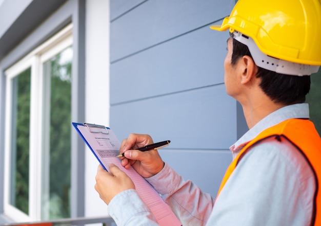 O inspetor ou engenheiro está verificando a estrutura do edifício e os requisitos da pintura de parede.