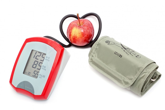 O instrumento para medir a mangueira de pressão em forma de coração. a apple é um símbolo da saúde.