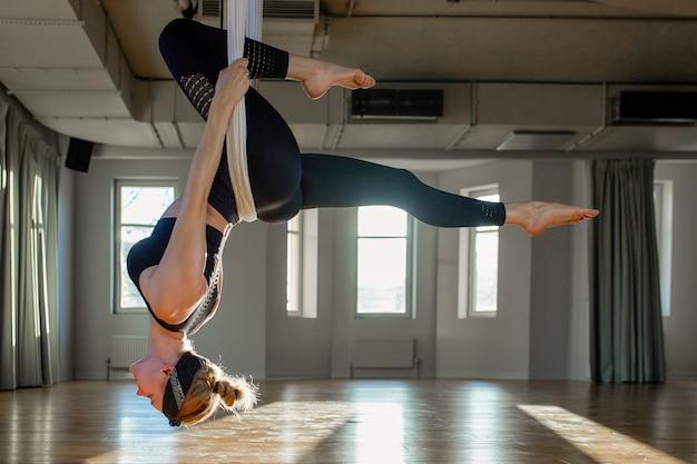 O instrutor aéreo da menina bonita mostra o medutiruet em linhas de suspensão de cabeça para baixo em uma sala de ioga. ioga do conceito, corpo flexível, estilo de vida saudável, aptidão.