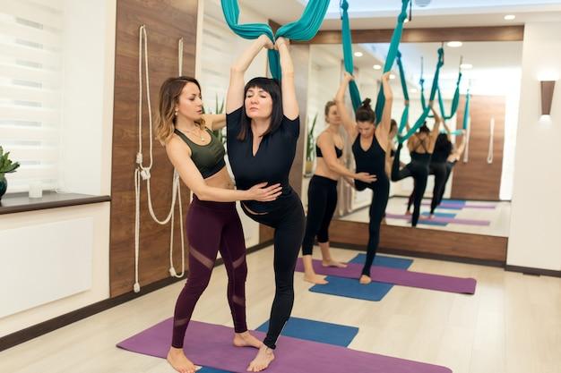 O instrutor ajuda a manter a postura quando mulher que faz a ioga da mosca que estica exercícios no gym.