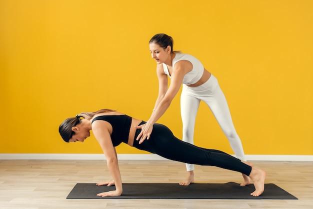 O instrutor da aula de ioga ajuda o iniciante a fazer exercícios de asana. feliz aula de ioga com um treinador.