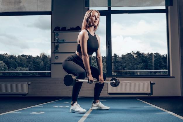 O instrutor de fitness mostra como fazer o exercício de levantamento terra