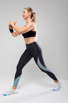 O instrutor de fitness mostra exercícios para o corpo em um fundo cinza.