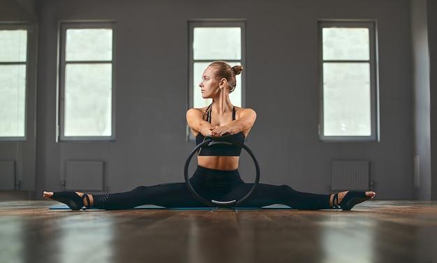 O instrutor de fitness mostra os exercícios com um expansor de borracha. motivação para um corpo bonito. banner de aptidão, espaço de cópia.