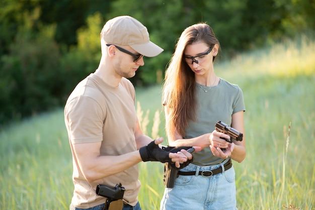 O instrutor ensina a garota a disparar uma pistola ao alcance