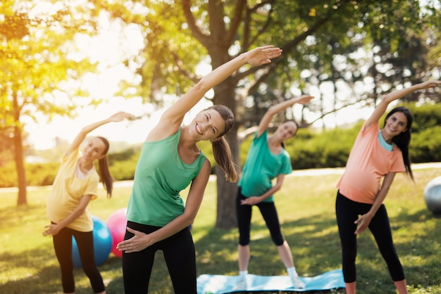 O instrutor mostra o lado das inclinações. barriga de fitness ao ar livre.