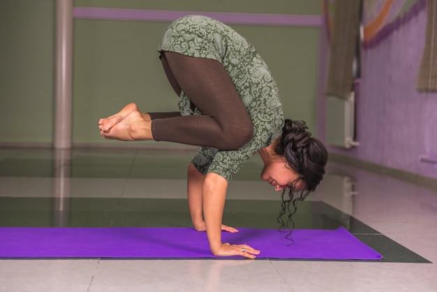 O instrutor profissional de ioga faz exercícios de asana.