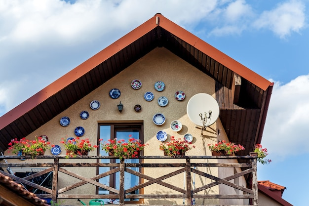 O interessante exterior de uma casa com vasos de barro para flores contra um céu azul. a parede é decorada com placas de cerâmica.