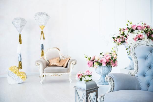 O interior chique e o ambiente aconchegante em uma sala vazia com poltronas com vasos de flores e decoração