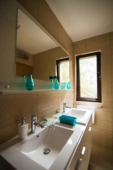 O interior da casa de banho lavatório bidé sanita espelho grande as paredes são de cor castanha clara