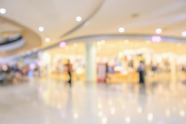 O interior da loja de departamentos de um shopping center de luxo moderno desfocar o fundo desfocado abstrato com luz bokeh