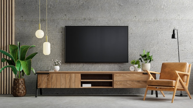 O interior da sala de estar tem armário de tv e poltrona de couro em uma sala de cimento com parede de concreto.
