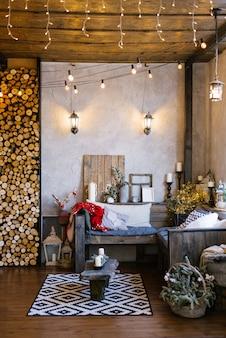 O interior de uma casa de campo, decorada para o natal e o ano novo. sofá com almofadas e lâmpadas retrô na sala