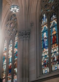 O interior de uma igreja com paredes cinza e pinturas em mosaico de santos religiosos nas janelas
