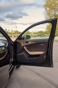 O interior do carro é preto, o banco do motorista é de couro marrom e bege.