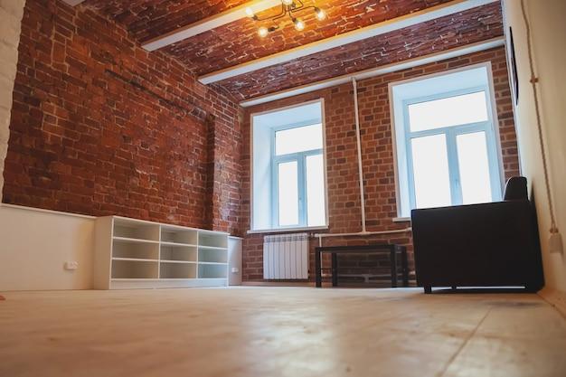 O interior do quarto é projetado em estilo loft, com parede e móveis decorativos de tijolo vermelho