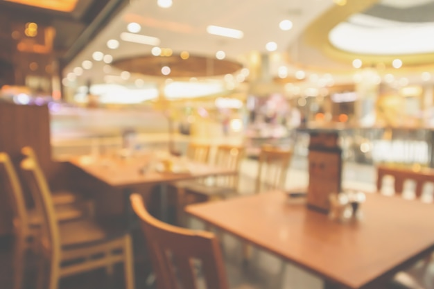 O interior do restaurante com o cliente e a mesa de madeira desfoca o fundo abstrato com a luz do bokeh