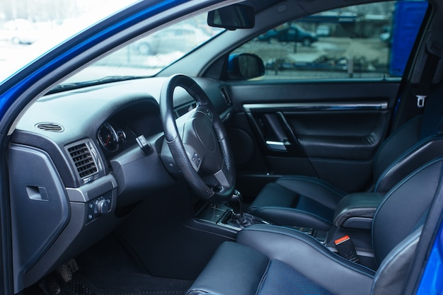 O interior do veículo com a porta da frente aberta, o assento do volante