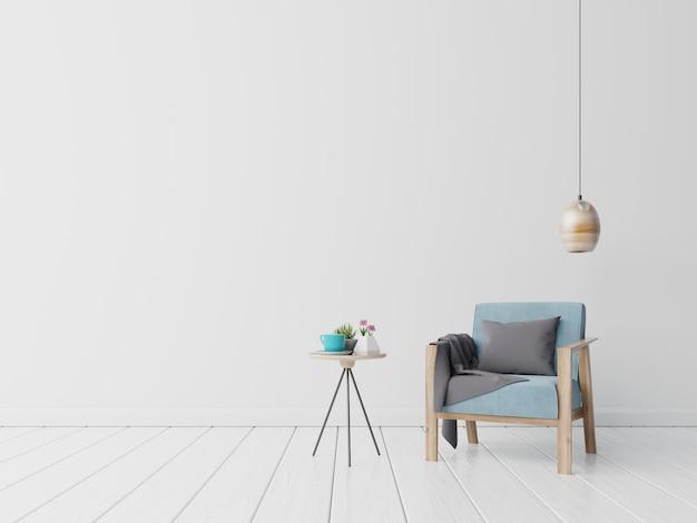 O interior tem uma poltrona azul e flor, lâmpada, mesa no fundo da parede branca vazia