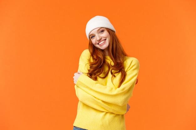 O inverno é sua estação favorita. concurso mulher ruiva boba e adorável abraçar-se e inclinar a cabeça