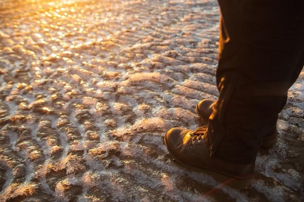 O inverno está chegando. botas femininas na superfície de gelo de chinelo áspero. uma mulher com sapatos de couro marrom, caminhando na costa do mar de inverno.