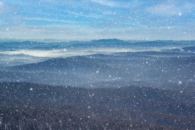 O inverno lindo desfocou o fundo das montanhas com neve caindo