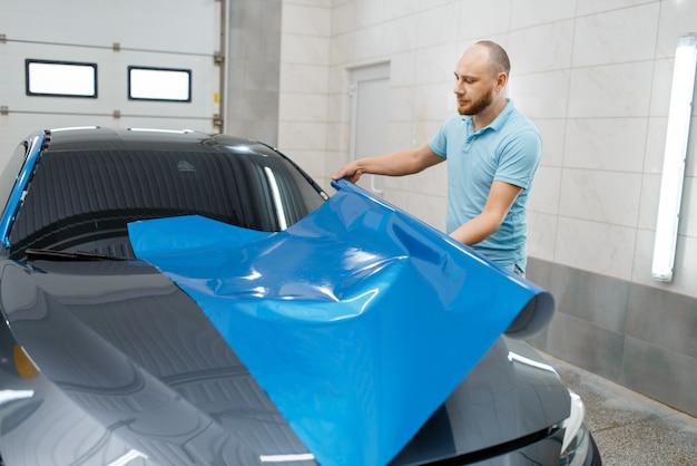 O invólucro de carro masculino contém uma folha de vinil de proteção ou rolo de filme. trabalhador faz detalhamento de automóveis. revestimento de proteção de pintura automotiva, ajuste profissional
