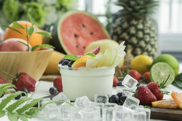 O iogurte de salada de frutas na tigela de vidro