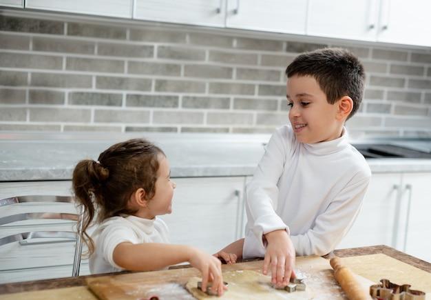 O irmão e a irmã sorriem um para o outro enquanto preparam biscoitos de natal
