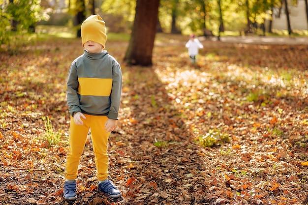 O irmão está brincando de esconde-esconde com uma menina em um parque de outono com folhagem dourada caída.