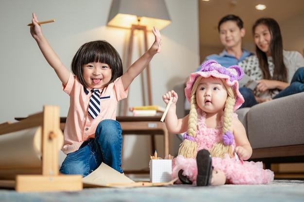 O irmão estava brincando com a irmã. ele ergueu a mão e riu da irmã mais nova no tapete