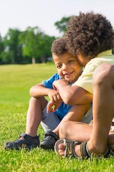 O irmão mais velho está contando um segredo para o mais novo em uma clareira ensolarada