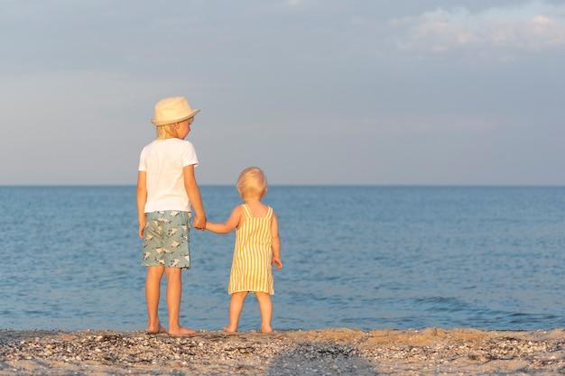 O irmão mais velho segura a irmã mais nova pela mão e olha para o mar